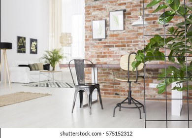 Loft interior with dining table, brick wall and green plant