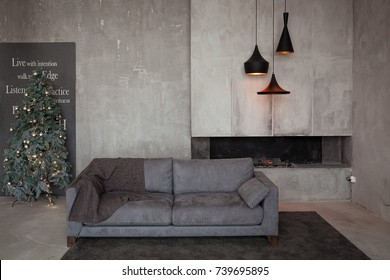 Loft Interior With Grey Concrete Walls, Fireplace, Black Chandeliers, Velor  Sofa And Decorated
