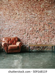 Loft interior mock up photo. Brown red brick wall with leather sofa and minimalist wooden table. Background photo with copy space for text. Vertical shot