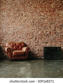 Loft interior mock up photo. Brown red brick wall with leather sofa and vintage wooden and metal trunk. Background photo with copy space for text. Vertical