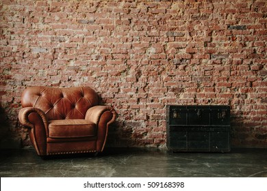Loft interior mock up photo. Brown red brick wall with leather sofa and vintage wooden and metal trunk. Background photo with copy space for text. Horizontal