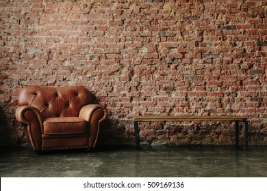 Loft interior mock up photo. Brown red brick wall with leather sofa and minimalist wooden table. Background photo with copy space for text. Horizontal