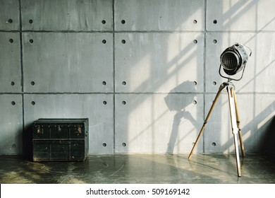 Loft interior mock up photo. Cement wall with retro lamp and vintage wooden and metal trunk. Background photo with copy space for text. Vertical