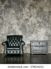 Loft interior mock up photo. Grey concrete textured wall with leather black chair and vintage wooden trunk. Background photo with copy space for text.