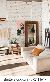 Loft interior with sofa, mirror, wahite brick wall, painting, flowers in pot.