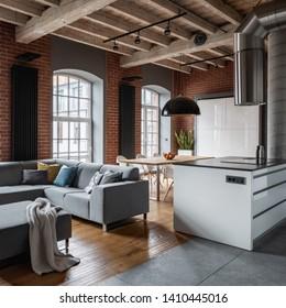 Loft interior with wooden ceiling, corner sofa and kitchen island