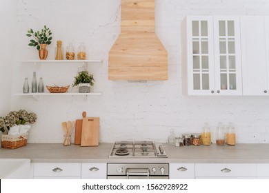 Loft Kitchen Cabinet and Worktop with White Brick Wall Background. Apartment Counter in Contemporary Clean Home. Modern Interior for Cooking. Countertop in Dining Residence with Flower Decor