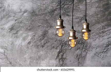 Loft pendant lamps on the background of rough cement plaster on the wall. Minimal loft interior. Edison light bulbs. 3d rendering.