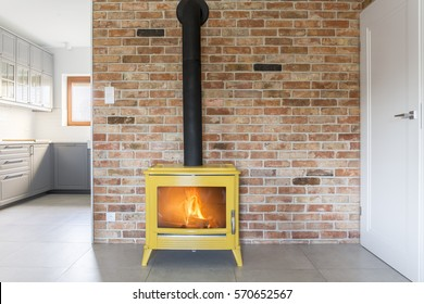 Loft with red brick wall and yellow freestanding stove