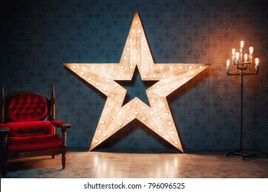 Loft room. Beautiful decor. Wooden star with lamps and leather armchair in a dark room