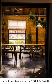Loft space design, wooden table, concrete flooring, brick wall, live plants. Industrial creative minimalistic cafe interior, simplicity concept, warm brown yellow colors