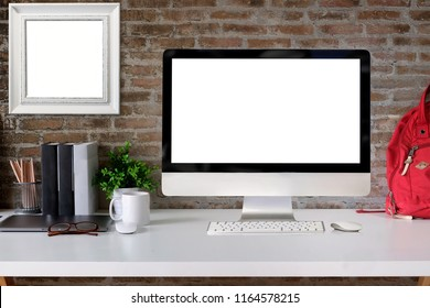 Loft student workspace with blank screen desktop computer on white wood desk.