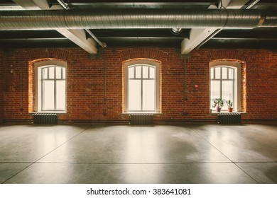 Loft studio Interior in old house. Big windows, brick red wall