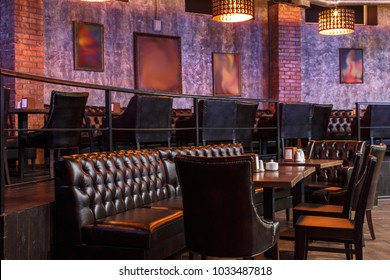 loft style bar interior with brown leather seats and leather armchairs, wooden tables