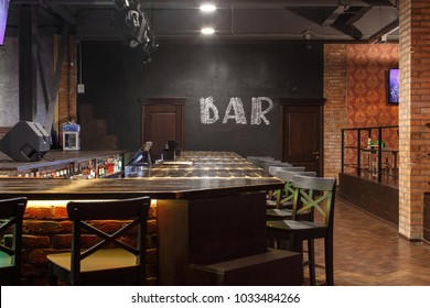 loft style bar interior with wooden countertop, bar chairs, bricks wall