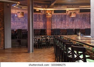 loft style bar interior with wooden countertop, bar chairs, bricks wall