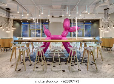Loft style cafe with light walls and black and white tiles on the floor. There are wooden racks with chairs around a big pink inflatable dog, green armchairs, hanging glowing lamps. Horizontal.
