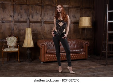 Loft style interior. attractive girl in fashionable clothes is standing in full growth in the Urban apartment