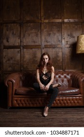 Loft style interior. sexual woman sits on a leather sofa in an expressive pose, looks at the frame. Urban apartment.