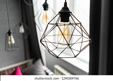 loft style iron lampshade with a light bulb in the interior living room in modern apartment. Vintage style light bulbs. glass round bulbs with a spiral on wall
