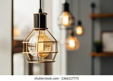 Loft style light bulbs glowing near window. Warm light. Coffee shop interior.