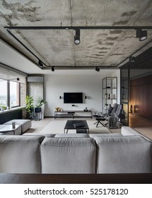 Loft style sitting-room with white, brick and concrete walls. There is sofa, tables, chair, armchair, shelves, speakers, TV and rack under it, lamps. On the floor there is a parquet and carpet.