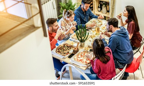 Loft view of happy friends eating pizza and toasting beer at home - Happy people having fun at dinner together - Friendship concept - Focus on men faces - Warm contrast filter