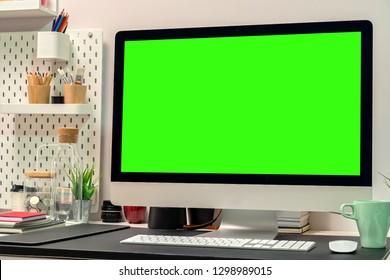 Loft workspace with green screen desktop computer