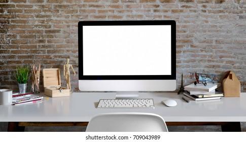 Loft workspace : Hipster or designer or artist desk work Blank screen desktop computer, craft tools, dummy, and supplies in retro brick wall.