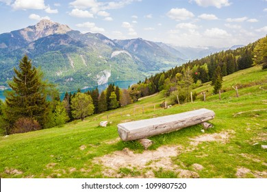 Log bench on a slope of a mountain Zwoelferhorn in austrian alps. Beautiful view of Wolfgangsee lake and Schafberg mountain on a sunny spring day.