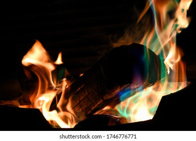 Log burning in colourful fire at night