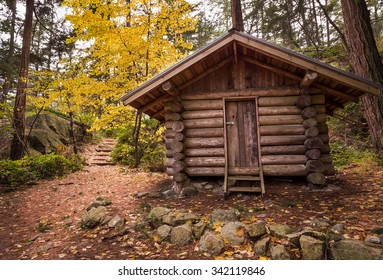 Log cabin in a forest in the fall.