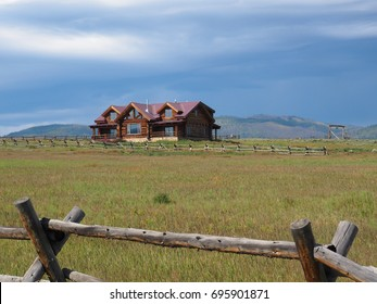 log cabin home on a prairie in rural Colorado in the Rockie Mountains Preserve.   Behind the home are mountains.  The prairie is surrounded bhy a rustic wood fence.