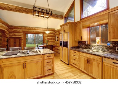 Log cabin kitchen interior design with large honey color storage combination and stone counter tops. View of dining area. Northwest, USA