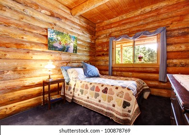 Log cabin rustic bedroom with blue curtains and large logs.