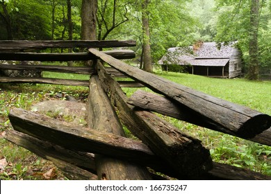 A log cabin in the woods with a split-rail fence in front.  Noah Ogle Cabin, Great Smoky Mountains National Park, near Gatlinburg, TN, USA.