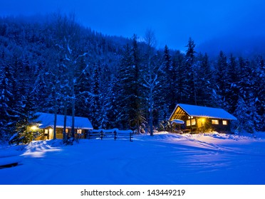 Log cabins glowing in the dusk surrounded by snow.