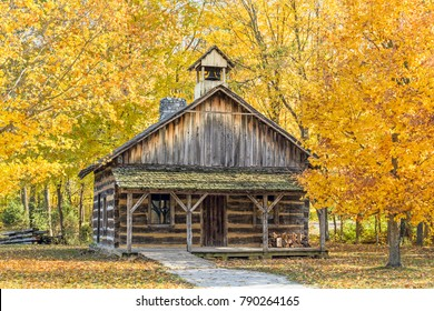A log church is surrounded by colorful autumn trees in an Indiana park.