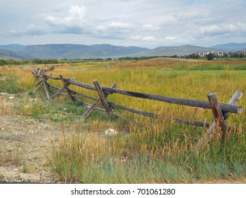 A log fence by a prairie in Colorado.   In the background are the Rocky Mountains.