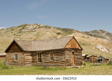 Log home in the ghost town at Bannack State Park in Montana.  The small buildings in the background were part of Bachelors Row.