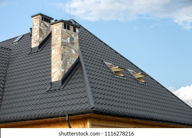 Log house in the mountains with a roof made of tiles and stone chimneys.