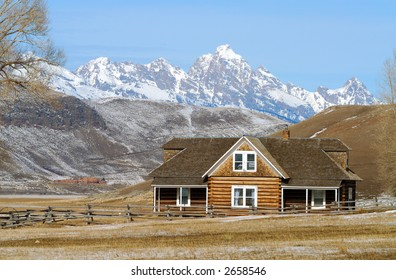 Log House With Snow Covered Mountains in Background