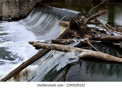 A log jam atop of Horlick dam in Racine Wisconsin on a cold January  day with ice formations on the logs with running water in the background.
