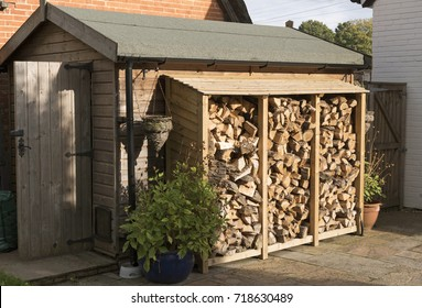 Log store standing against a garden shed. Logs stacked in a garden. UK