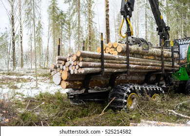 Log truck working. The harvester working in a forest. Logger with robotic arm lifts logs in winter woods