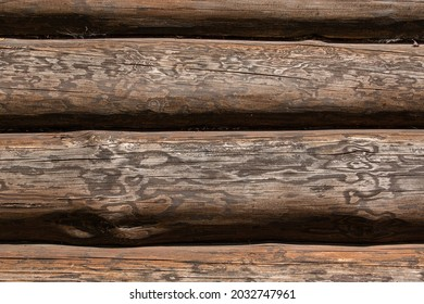 Log wall of a dark wooden blockhouse house close-up.