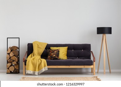 Log of wood next to comfortable sofa with yellow blanket and pillows, stylish wooden lamp with black lampshade, real photo copy space on the empty grey wall