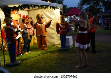 Logan City, Queensland / Australia - December 15 2018: People having pictures taken with Christmas mascots at the City of Logan Christmas Carols