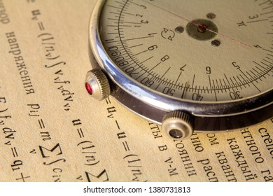 Logarithmic ruler closeup on a background of the scientific literature. Subject for scientific activity on the background of the old book page with mathematical formulas. View with space for your text