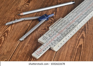 Logarithmic ruler, compasses, pencil on a wooden table. Stationery for engineers and students.